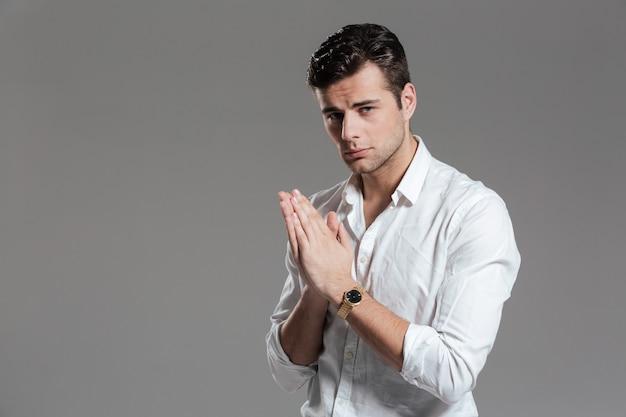 Portret van een succesvolle jonge man gekleed in wit overhemd