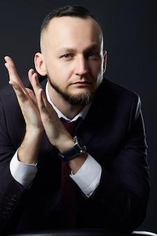 Portret van een succesvolle mannelijke zakenman op een donkere muur