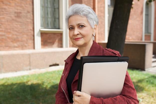 Portret van een succesvolle rijpe zakenvrouw in stijlvolle kleding buitenshuis poseren