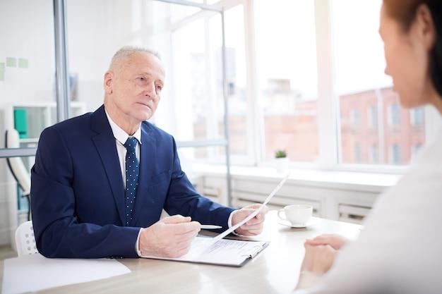 Portret van een succesvolle senior zakenman interviewen jonge vrouw voor baan in kantoor