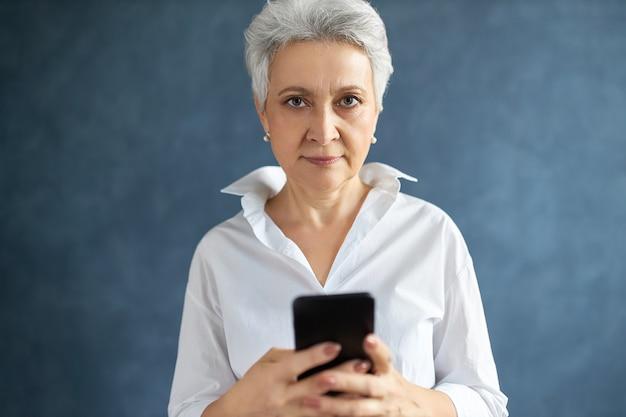Portret van een succesvolle vrouwelijke uitvoerende macht van middelbare leeftijd met kort grijs haar tekstbericht aan het typen op haar mobiele telefoon