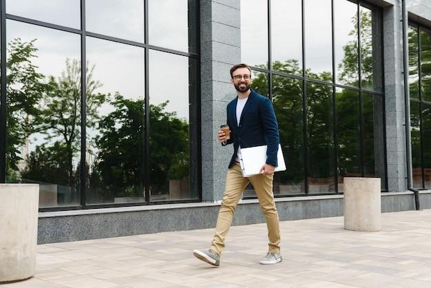 Portret van een succesvolle zakenman die een bril draagt die laptop en een papieren beker houdt tijdens het buiten lopen in de buurt van het gebouw