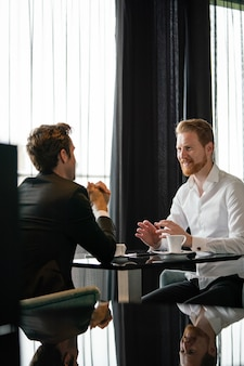 Portret van een succesvolle zakenman die lacht terwijl hij de deal met zijn partner bespreekt tijdens een ontmoeting tijdens de koffiepauze