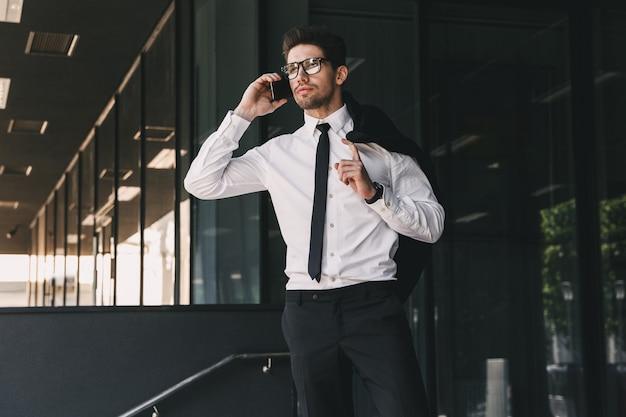 Portret van een succesvolle zakenman gekleed in formeel pak staande buiten glazen gebouw met jas over zijn schouder, en praten over de mobiele telefoon