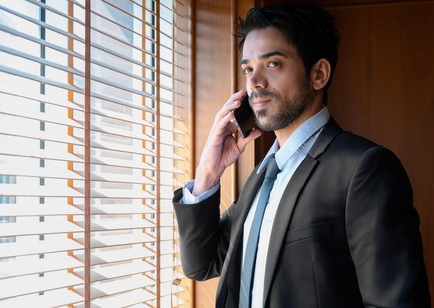 Portret van een succesvolle zakenman in marineblauw pak zaken praten op de mobiele telefoon terwijl hij naast het raam op kantoor staat