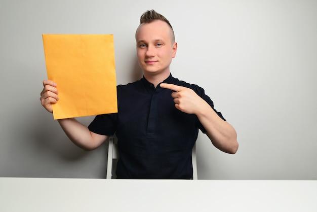 Portret van een succesvolle zakenman met een gele map op een witte achtergrond