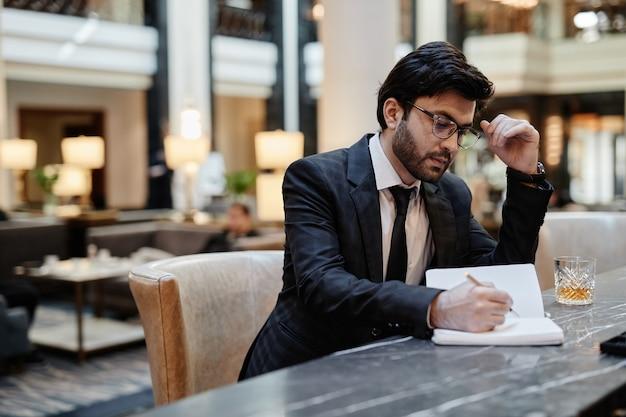 Portret van een succesvolle zakenman uit het midden-oosten die tijdens een zakenreis in de hotellobby werkt, kopieer ruimte