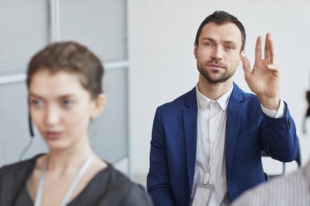 Portret van een succesvolle zakenman-zakenman en hand opsteken om vragen te stellen terwijl hij in het publiek zit op een zakelijke conferentie of seminar, kopieer ruimte