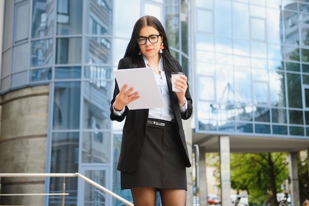 Portret van een succesvolle zakenvrouw gaan werken met koffie wandelen in de buurt van kantoorgebouw op straat in de stad