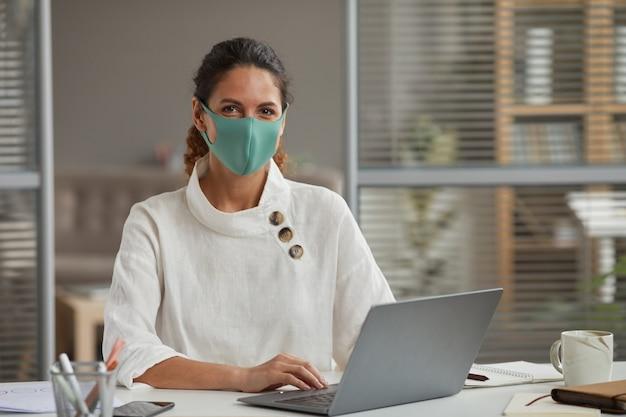 Portret van een succesvolle zakenvrouw masker dragen en camera kijken tijdens het gebruik van laptop en werken aan de balie in kantoor, kopieer ruimte