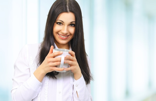 Portret van een succesvolle zakenvrouw met een kopje koffie op keerzijde