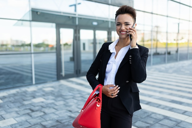 Portret van een succesvolle zakenvrouw op de achtergrond van een wolkenkrabber