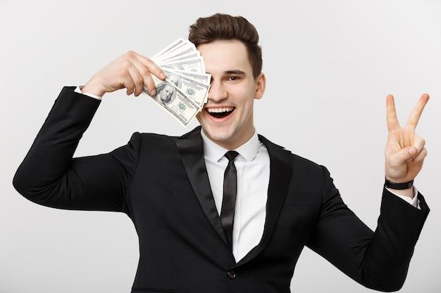 Portret van een succesvolle zelfverzekerde man die een hoop geldbankbiljetten toont en een overwinningsvingerteken toont dat op een witte achtergrond wordt geïsoleerd