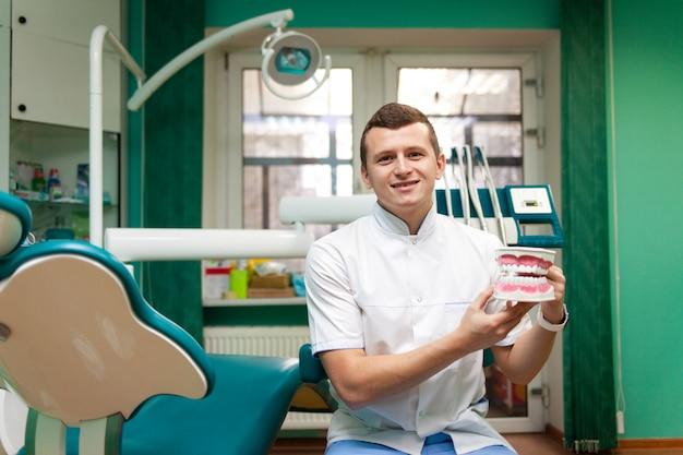Portret van een tandartsarts die in handen het model van de kaak houdt om het juiste borstelen te simuleren