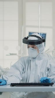 Portret van een tandartsassistente die op het toetsenbord van de computer typt en een beschermingsuniform draagt met gezichtsschild, masker, handschoenen en overall. stomatologieverpleegkundige die monitortechnologie gebruikt in de mondkliniek