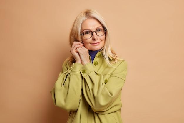 Portret van een tedere vrouw van middelbare leeftijd houdt handen in de buurt van gezicht kijkt rechtstreeks naar de camera met kalme uitdrukking