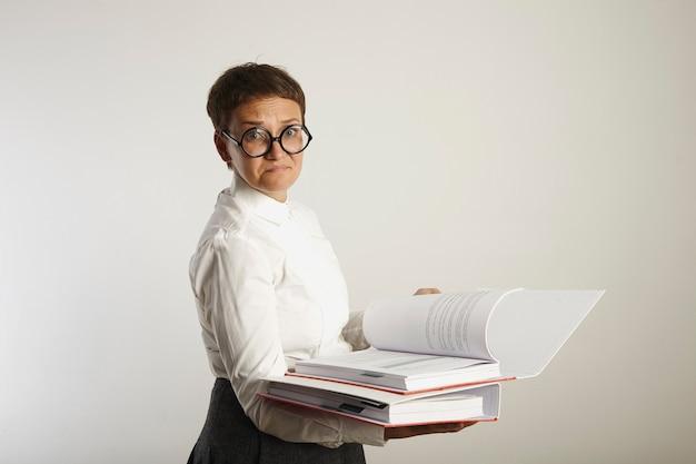 Portret van een teleurgestelde en verdrietige vrouwelijke leraar in ouderwetse outfit met twee dikke rode en witte mappen op een witte muur