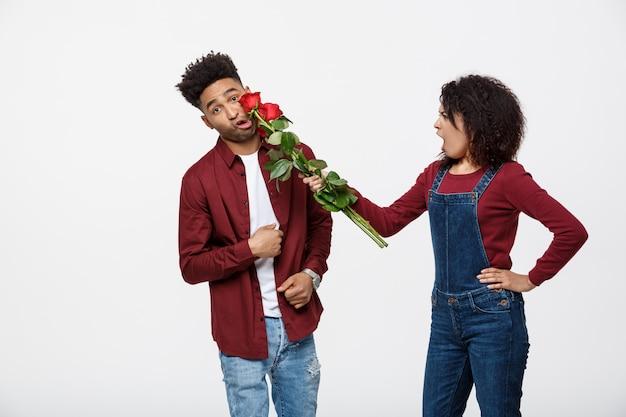 Portret van een teleurgestelde jonge vrouw met rode roos, terwijl boos op haar vriendje.