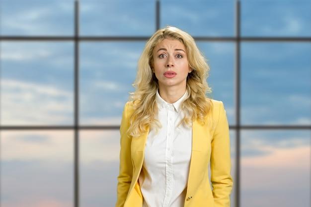 Portret van een teleurgestelde jonge vrouw. mooie boos blonde kijkt verward op blauwe hemel loket. menselijke gezichtsuitdrukkingen.