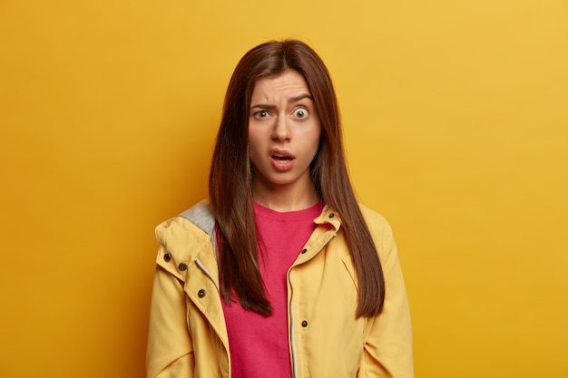 Portret van een teleurgestelde, ongelukkige vrouw heeft een ongelukkige reactie verrast, trekt wenkbrauwen op, grijnst gezicht bij het zien van iets onaangenaams