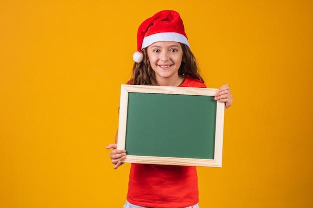 Portret van een tevreden blank meisje in een kerstmuts met een spandoek met ruimte voor tekst.
