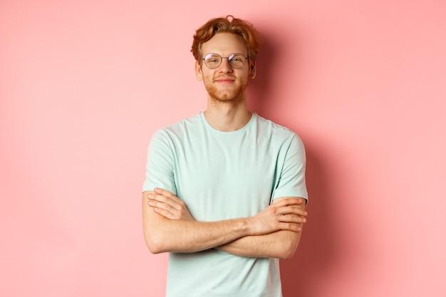 Portret van een tevreden blanke man met rood haar en baard, armen over elkaar op de borst en lachend met een zelfvoldaan gezicht, een bril op, staande over een roze achtergrond.
