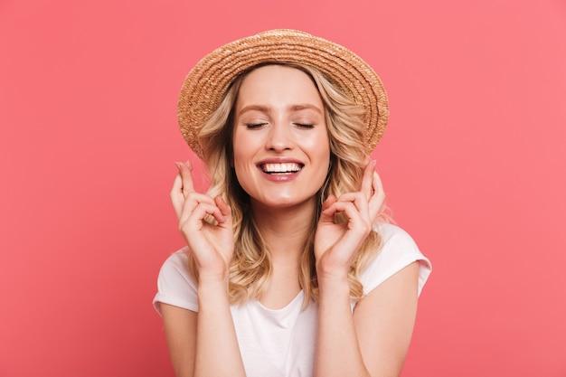 Portret van een tevreden blonde vrouw met een strohoed die vingers gekruist houdt en geluk wenst, geïsoleerd over roze muur