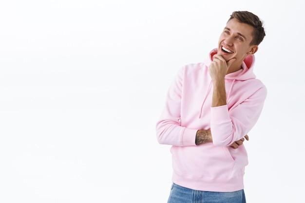Portret van een tevreden creatieve, attente knappe man heeft een interessant idee, kijkt naar een grafiek of kiest een product in de winkel, staart naar lege ruimte peinzend met een tevreden glimlach, witte muur