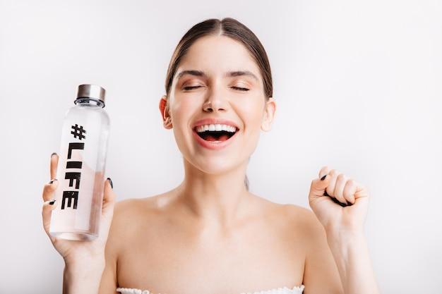 Portret van een tevreden dame zonder make-up, poseren met plezier in een geweldige sfeer met een fles water op geïsoleerde muur.