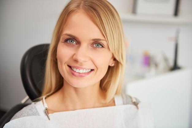 Portret van een tevreden en lachende vrouw in de tandartskliniek