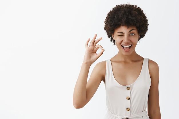 Portret van een tevreden en zelfverzekerde emotionele vrouw met een donkere huid en een afrokapsel die met hint knipogen en glimlachen terwijl ze oke gebaar toont