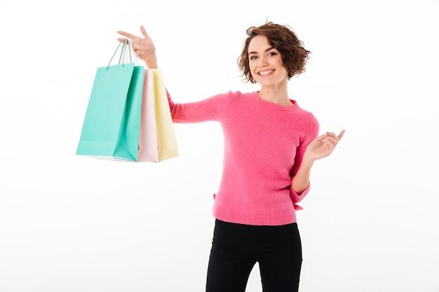 Portret van een tevreden gelukkig meisje dat het winkelen zakken toont