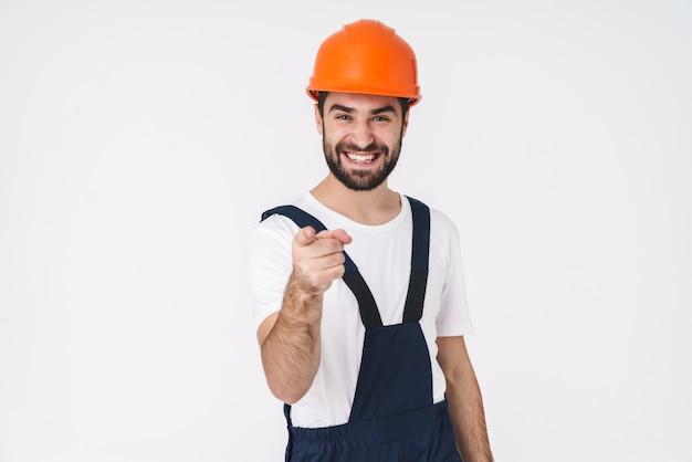 Portret van een tevreden gelukkige jonge man bouwer in helm poseren geïsoleerd over witte muur wijzend naar jou.