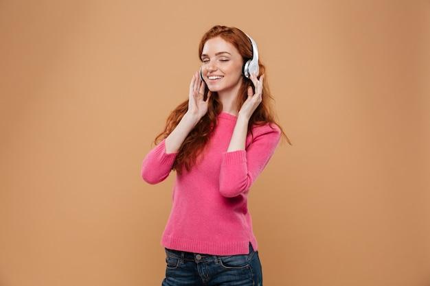 Portret van een tevreden glimlachende roodharigemeisje het luisteren muziek met hoofdtelefoons