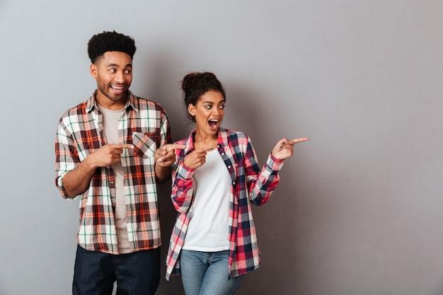 Portret van een tevreden jong afrikaans paar die kant met vingers richten