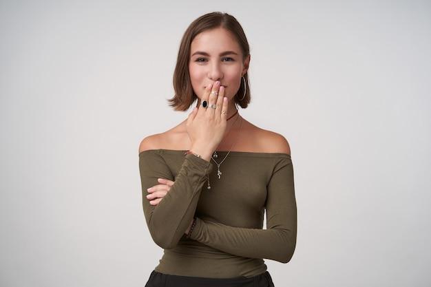 Portret van een tevreden jong bruinharig wijfje dat positief naar de voorkant kijkt en een opgeheven handpalm op haar mond houdt, staande tegen een witte muur in vrijetijdskleding