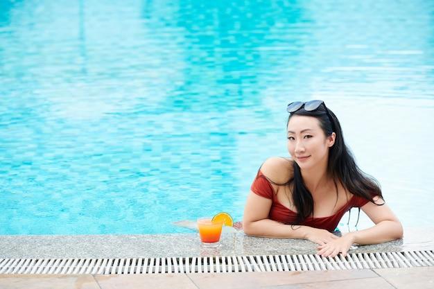Portret van een tevreden jonge aziatische vrouw met een zonnebril op het hoofd leunend op de rand van het zwembad
