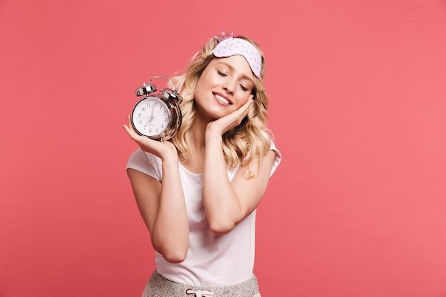 Portret van een tevreden jonge vrouw die een slaapmasker draagt met een wekker na het ontwaken, geïsoleerd over de rode muur