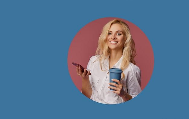 Portret van een tevreden jonge vrouw die mobiele telefoon met behulp van terwijl het houden van kop van koffie om te gaan. gluren van het klassieke blauwe cirkelgat in de muur. selfie maken en glimlachen