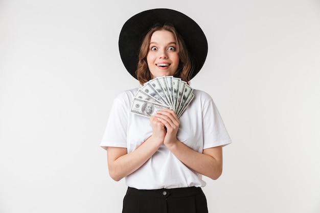 Portret van een tevreden jonge vrouw gekleed in zwarte hoed