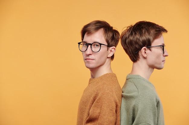Portret van een tevreden jongeman in een mosterdtrui en een bril die rug aan rug staat met tweelingbroer tegen een oranje achtergrond