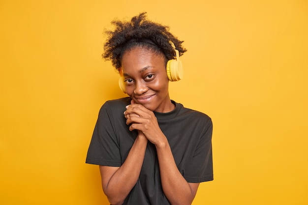 Portret van een tevreden knappe afro-amerikaanse tiener die verlegen is, houdt de handen in de buurt van het gezicht kijkt tevreden naar de camera