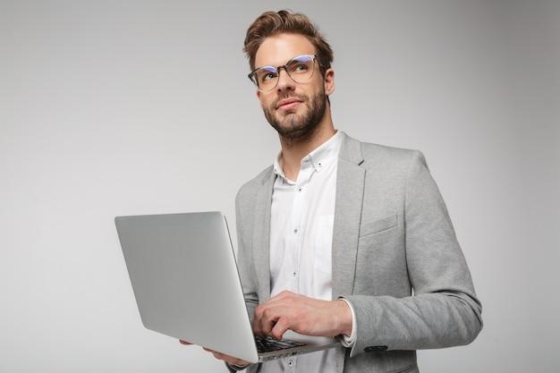Portret van een tevreden knappe man in een bril die een laptop vasthoudt en gebruikt die over een witte muur wordt geïsoleerd