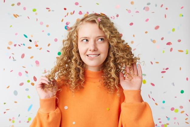 Portret van een tevreden meisje dat denkt naar zijspelen met haar haar, bijt op haar lip, staat onder de vallende confetti