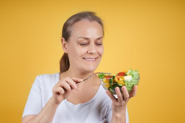 Portret van een tevreden rijpe vrouw in een wit overhemd met een bord salade en een vork, klaar voor het avondeten