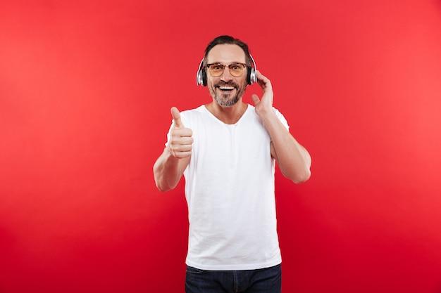 Portret van een tevreden volwassen man luisteren naar muziek
