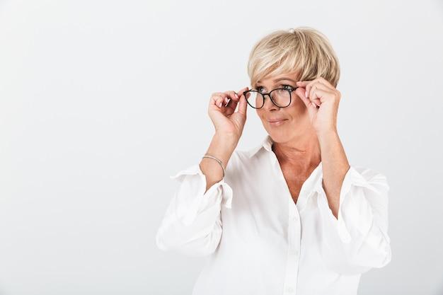 Portret van een tevreden volwassen vrouw die een bril vasthoudt en naar een camera kijkt die over een witte muur in de studio wordt geïsoleerd