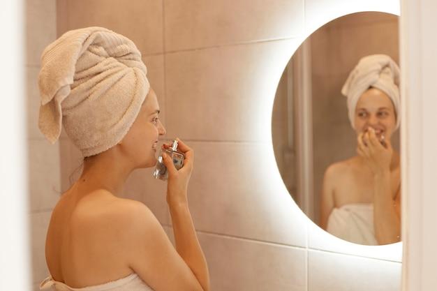 Portret van een tevreden vrouw die parfum ruikt terwijl ze in de badkamer poseert, geniet van een aangename geur, staande met blote schouders en witte handdoek op haar haar voor de spiegel.