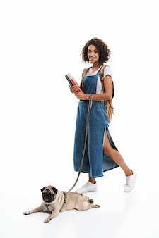 Portret van een tevreden vrouw met een rugzak die boeken vasthoudt en in evenwicht is met haar mopshond geïsoleerd over een witte muur