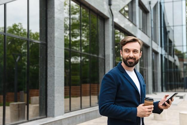 Portret van een tevreden zakenman in een jas die een mobiele telefoon vasthoudt terwijl hij buiten in de buurt van een gebouw staat met afhaalkoffie